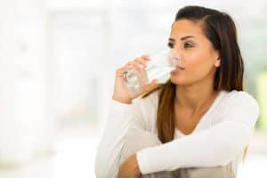 Frau trinkt Wasser aus dem Wassersprudler
